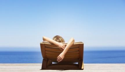 mujer-recostada-en-un-camastro-frente-al-mar
